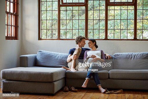 Loving expectant couple sitting on sofa at home