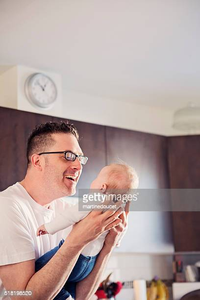 Loving father holding and looking at baby in kitchen.