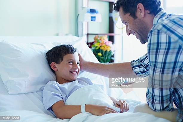 Loving father with ill son in hospital ward