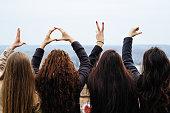 Four friends show love hands