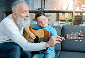 Transmitting knowledge. Joyful senior man beaming while spending his time with an adorable grandson and showing him how to play guitar.