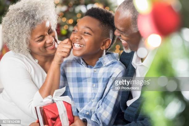 Loving grandma pinches her grandson's cheeks at Christmastime