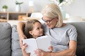Loving grandmother teaching granddaughter holding book sitting on sofa, grandma baby sitter embracing kid girl reading fairytale to cute child, nanny granny telling story to preschool grandchild