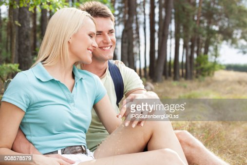 Loving hiking couple smiling while relaxing in forest : Stockfoto