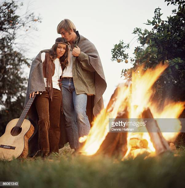 Loving hippie couple standing by bonfire