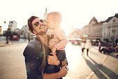 Loving little boy kissing his happy father in the city.