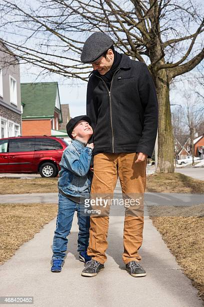 Loving little boy with Down Syndrome hugs his dad.