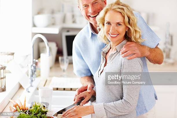 Loving mature couple preparing food together in the kitchen