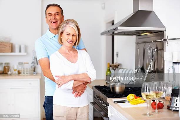 Amour mature homme embrassant femme par derrière dans la cuisine
