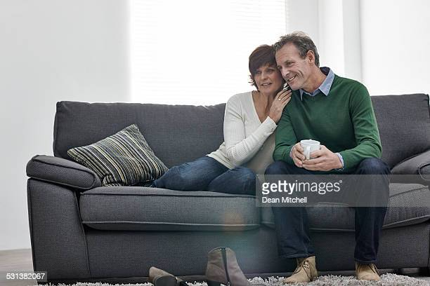 Loving middle aged couple sitting together on sofa