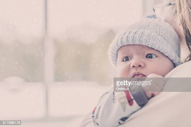 Loving Mom With Newborn Baby Close to Window in Winter