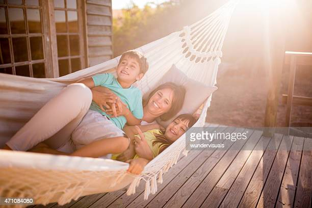 Loving mother and children laughing together in a hammock