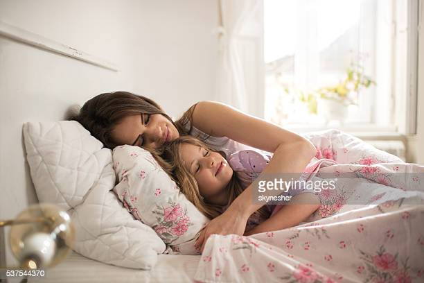 Loving mother and daughter sleeping in bed together.