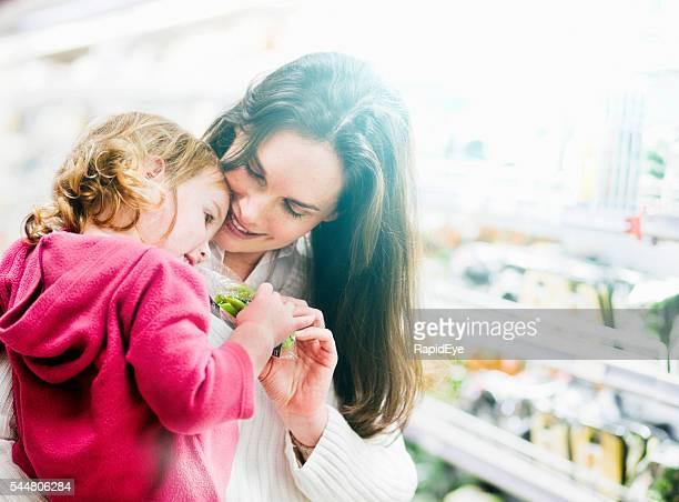 Amorevole madre e piccola figlia sorridente nel supermercato