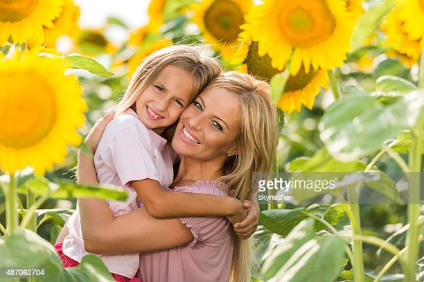 Loving mother embracing her daughter among sunflowers.