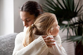 Loving mother hugging cute little girl, young woman embracing adopted child holding tight, sincere warm relationships between mum and daughter cuddling, moms love and care or adoption concept