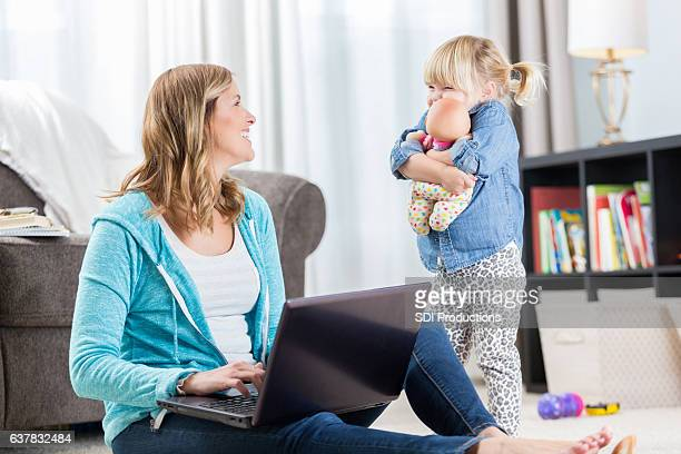 Loving mother smiles at daughter while using laptop