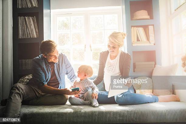 Loving parents showing technologies to baby at home