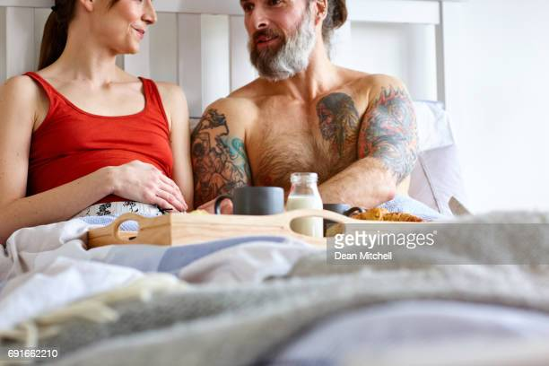 Loving pregnant couple on bed with breakfast