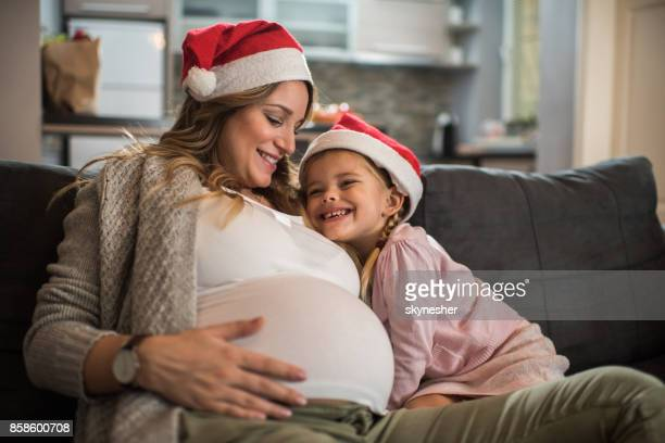 Loving pregnant mother and daughter spending winter holidays at home.