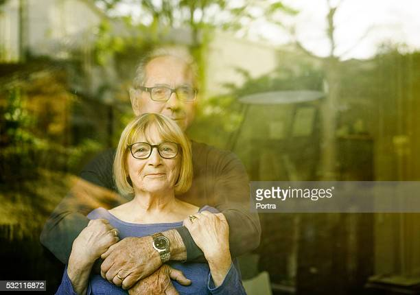 Loving senior couple seen through glass window