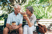 Loving senior couple sitting on a park bench having coffee and muffins. Tourist relaxing outdoors on a park bench.