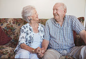 Senior couple sitting together hand in hand on the sofa. happy mature couple looking relaxed and content together.