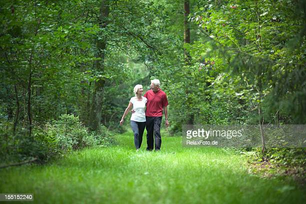 Loving senior couple walking through forest in summer