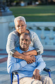 An affectionate senior African American couple at the park. The man is sitting in a wheelchair.  His wife is standing behind him, embracing him, looking at the camera