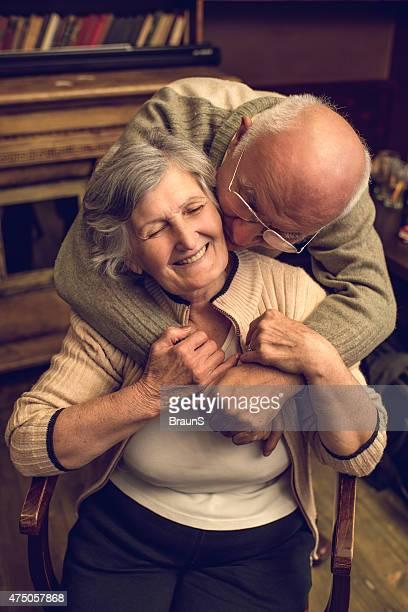 Amorevole uomo anziano baciare e abbracciare sua moglie a casa.