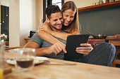 Couple smiling as they read a tablet computer together in morning in the kitchen. Young man and woman catching up on social media smiling. Woman hugging her boyfriend holding tablet PC.
