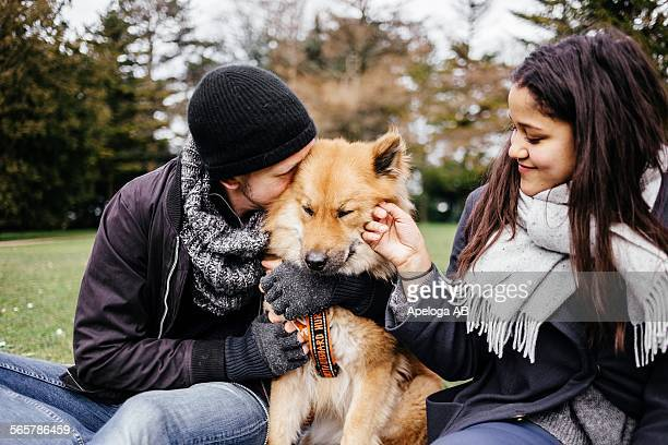 Loving young couple stroking Eurasier at park