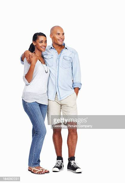 Loving young couple with arms around on white background