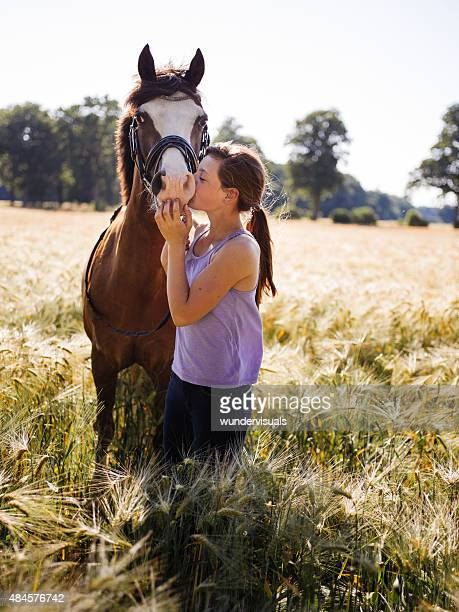 Lovingly girl giving her horse a kiss on it's nose