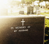 """A gravestone, anonymously inscribed """"In memory of my husband"""",  stands in a deserted cemetery."""