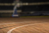 a basketball court from a low angle, focus on foreground, blurred out background.