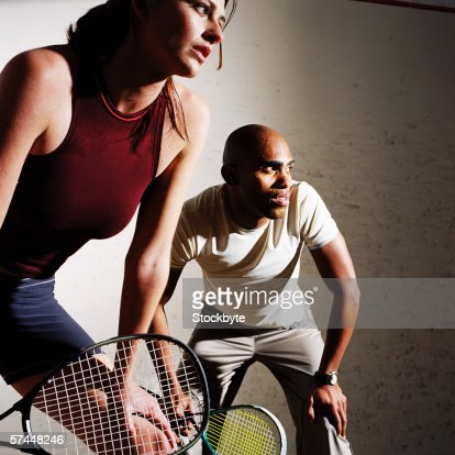low angle close-up of a couple playing a mixed doubles game of tennis