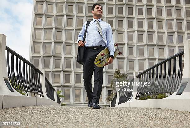 Low angle full length front view of mid adult business man carrying skateboard