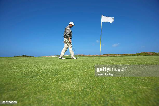 Low angle full length side view of golfer walking to golf flag, looking down