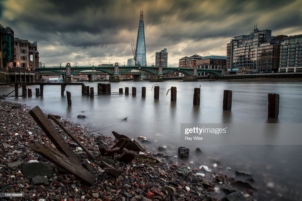 CONTENT] A low angle long exposure looking along the River Thames and back at the newly build Shard at London Bridge. It's sunset and the stormy looking skies are blurred by the long exposure dragging you into the frame.