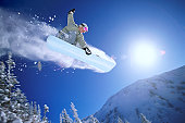 Low Angle Mid Air Shot of a Woman Snowboarding
