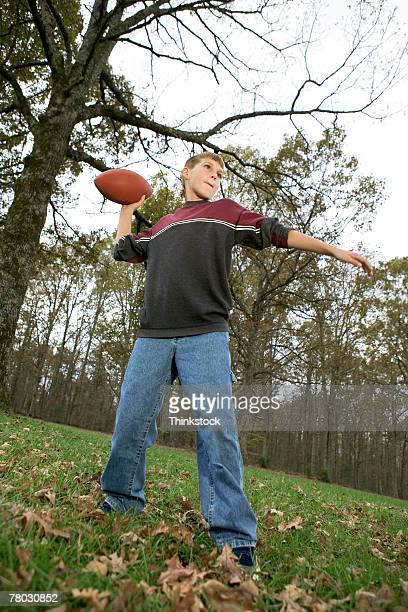 Low angle of a boy throwing a football in the yard.
