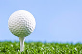A low angle view of a Golf ball sitting on white wooden tee against a blue sky, with grass underneath