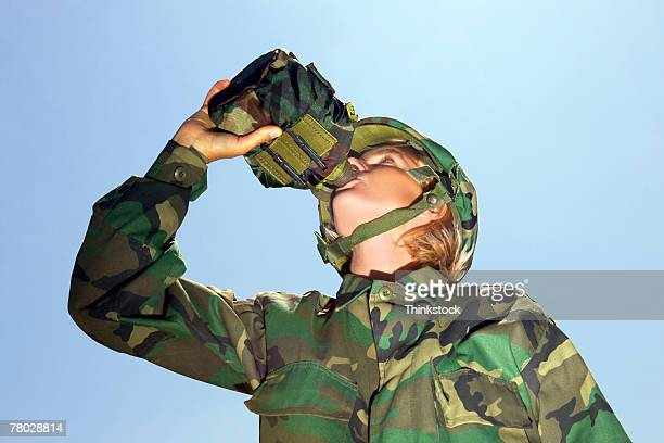 Low angle of a military soldier in camouflage drinking water.