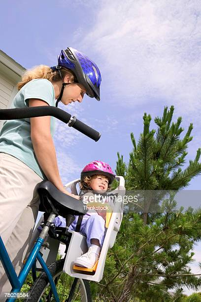 Low angle of a mother strapping her child into a bicycle seat; both are wearing helmets for safety