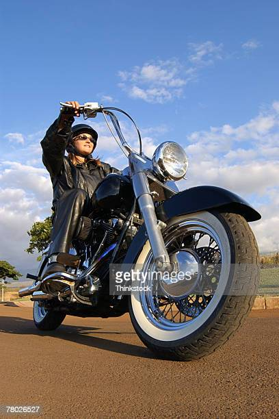 Low angle of a woman in leather riding a motorcycle.
