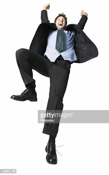low angle of a young caucasian man in a suit as he throws up his arms in celebration