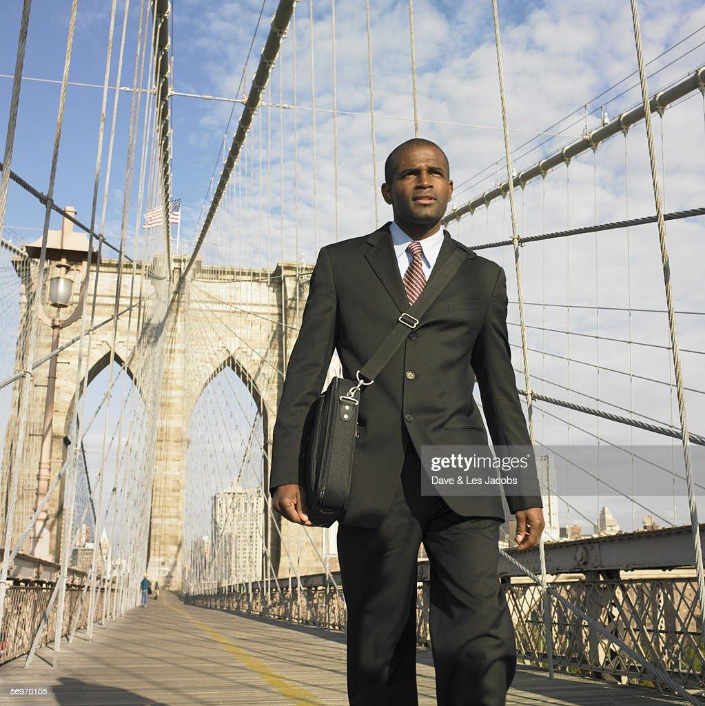 Low angle of businessman walking across bridge : Stock Photo