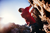 Low angle of extreme free climbing man hanging on rock