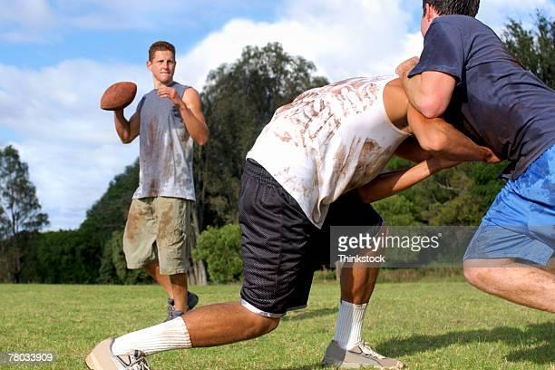 Low angle of three teen boys playing football